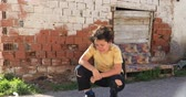 needy : Portrait of a caucasian poor young boy  infront of the slum and looking sadly Stock Footage