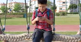 mladistvý : Portrait of a happy preteen boy using smartphone and swinging at the playground. Technology, internet communication and people concept, Smartphone addiction Dostupné videozáznamy