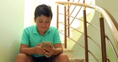 выражая позитивности : Preteen boy laying sofa with smartphone texting message or playing game at home. Technology, internet communication and people concept