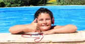 pre teen : Happy preteen boy in swimming pool listening to music  with headphone and relaxing on a sunny summer day