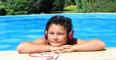 pre adolescente : Happy preteen boy in swimming pool listening to music  with headphone and relaxing on a sunny summer day