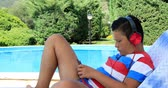 expressando positividade : Portrait of a cute teenage boy with headphone sitting on a sunbed near the swimming pool and using smartphone on a sunny summer day. Technology, internet communication and people concept, smartphone addiction
