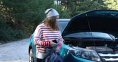 сломал : Portrait of a troubled woman  talking by smartphone near broken car with open hood Стоковые видеозаписи