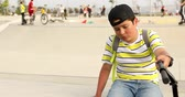 Handsome unhappy preteen boy with scooter sitting alone at the skateboard park