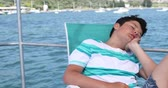 Portrait of a sleepy, tired teenager traveler lying on yacht deck at summer vacation