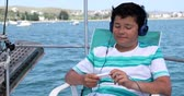 pre teen : Portrait of a happy cute handsome teenager traveler on a yacht deck with headphone listening to music at summer vacation