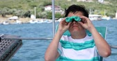 双眼鏡 : Portrait of a teenager traveler with binucular looking around on yacht deck at summer vacation. Looking at the camera and smiling