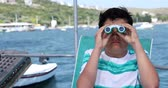 Portrait of a teenager traveler with binucular looking around on yacht deck at summer vacation