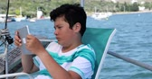 egész : Portrait of a caucasian teenager using digital tablet computer on deck at summer vacation Stock mozgókép