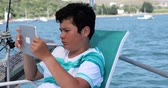 Portrait of a caucasian preteen schoolboy with digital tablet computer on boat deck at summer holiday