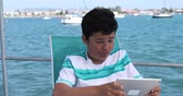 技術 : Happy teenager gaming with digital tablet computer on yacht deck at summer vacation