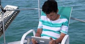 技術 : Portrait of a preteen schoolboy with digital tablet computer on boat deck at summer holiday