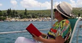 Portrait of a relaxed middle aged woman sitting luxury yacht deck travelling and reding a novel at summer vacation
