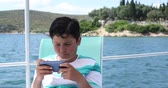 expressando : Portrait of a caucasian teenager playing video game with smartphone on yacht at sunny summer day