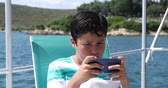 技術 : Portrait of a caucasian teenager traveling by yacht and playing video game with smartphone at sunny summer vacation day