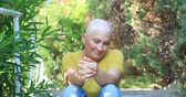 Portrait of a positive woman with cancer sitting at the outdoor and smiling to a camera