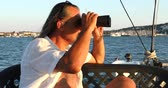 espião : Portrait of a middle aged businessman sits on sailing yacht looks through binoculars.  Marine, people, summer, vacation, travel,nature, tourism concept.