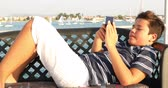 videospiel : Portrait of a caucasian teenager playing video game with smartphone on yacht at sunny summer day