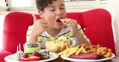ali di pollo : Portrait ofa caucasian teenage boy sitting at home and eating unhealthy foods. Filmati Stock