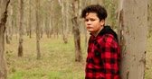 adolescencia : Portrait of a one caucasian teenage boy at the forest hiking looking at the camera seriously Archivo de Video