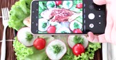 utensili da cucina : Female hands using smartphone to take photos of seafood plate