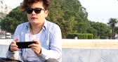 gönderme : Portrait of a relaxed teenage boy sitting at the city park with smart phone. Kid watching to screen, reading, typing, playing games. Technology, internet communication and people concept, Smartphone addiction