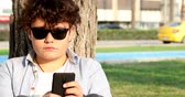 videospiel : Portrait of a relaxed teenage boy sitting at the city park with smart phone. Kid watching to screen, reading, typing, playing games. Technology, internet communication and people concept, Smartphone addiction