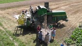 Drohobych, Ukraine - 04 July, 2018: Aerial view of combine harvester winnowing wheat into big bag held by people. Harvesting, countryside. Slow motion