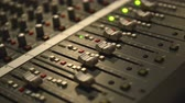 Analog audio mixing board with several channels and push buttons visible Stock Footage