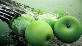 jugo de manzana : Green Apples under a stream of water with traces of transparent bubbles on a green background.