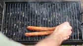 chargrilled : Placing sausages on the grill,close up.HD 1080p.GoProHERO3.