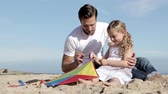 string : A father is sitting with his daughter on the beach as she winds up the string of a kite. They are talking and laughing.