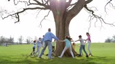 zaman : A group of Students and Teachers playing Ring-A-Rosie around a tree outdoors. Stok Video