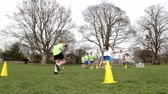 byt : Adults on grassed area with school children supervising a football training session, Everyone can be seen running around cones. School building can be seen in the background.