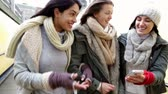 hat : Three young women walking together down towards an underpass with their arms linked, looking at something on a smartphone. Stock Footage