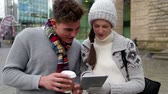hat : Young man and woman standing in the city using a digital tablet together.