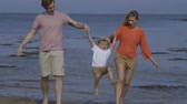 witalność : A happy little boy walks hand in hand with his parents along the beach. They are lifting him up and swinging his as they get closer to the camera. Wideo