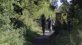 run : Young couple running together along a woodland path on a sunny day