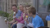 nabiał : Family of four enjoying ice-cream sitting on a bench outside. They are wearing casual clothing and laughing.