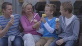 insalubre : Family of four enjoying ice-cream sitting on a bench outside. They are wearing casual clothing and laughing.