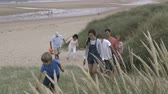 britský : A family are leaving the beach together. They are walking up the sand dunes smiling.