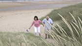 britský : An older couple are holding hand, walking up the sand dunes leaving the beach together.
