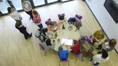 curiosidade : View from above of students and teachers in an educational room. some are sitting at the table making robots whilst others are standing and talking amongst themselves.