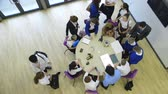 mecânico : View from above of students and teachers in a technology lesson. Some are sitting at the table whilst others are standing and talking amongst themselves.