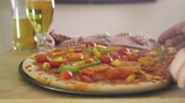 pizza cheese : Pan of a vegetable pizza and some beers. A hand can be seen taking a slice of the pizza.
