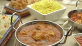 jedzenie : Pan view of indian and chinese food. There are curries and noodles with other accompanying foods on a wooden worktop.