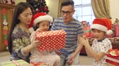 Chinese family on Christmas morning. The children are sitting on their parents laps, shaking the wrapped presents to try and work out what is inside.
