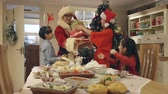 erişte : Chinese family about to eat a chinese christmas dinner when the father walks in dressed as Father Christmas and bearing presents.