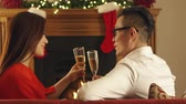 lareira : Chinese couple enjoying a glass of bubbly at Christmas. They make a peaceful toast. Stock Footage