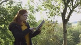 landscape : Young woman analysing nature. She is using a digital tablet to research. Stock Footage